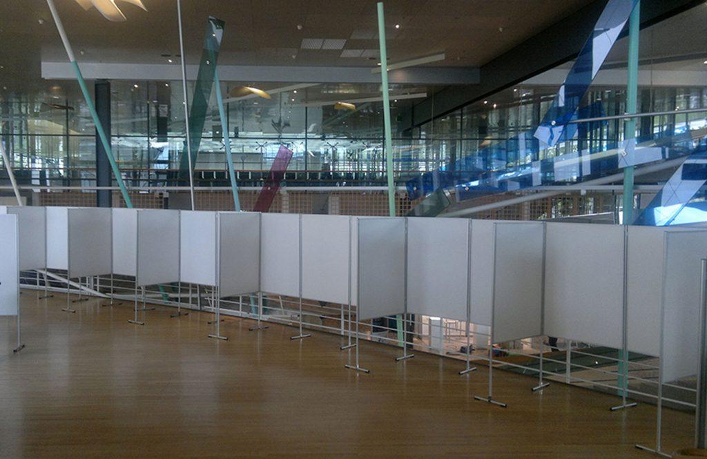 Weiße Combino Messewände stehen aneinander gereiht in einer Ausstellungshalle, sie bilden eine mobile und bespielbare Ausstellungswand.