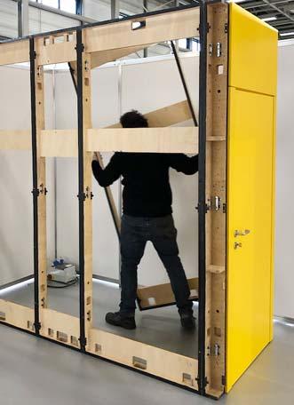 Ein Mitarbeiter trägt ein Wandelement eines Messestandes in eine kastenförmige Konstruktion.