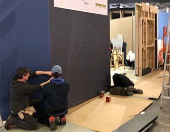 Zwei Mitarbeiter bearbeiten die Oberfläche einer Ausstellungswand.