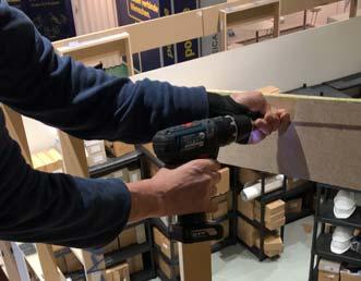 Close-up: Ein Mitarbeiter bedient einen Akkuschrauber und montiert ein Holzgerüst.