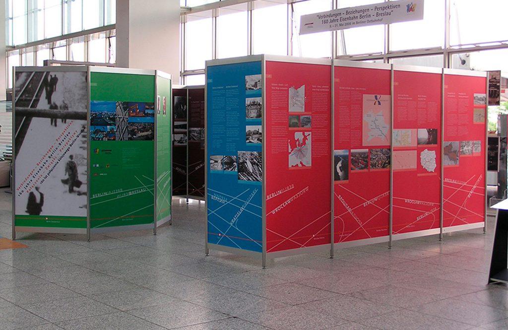 Octanorm Messetafeln in rot, blau und grün stehen nebeneinander in einem Ausstellungsraum.