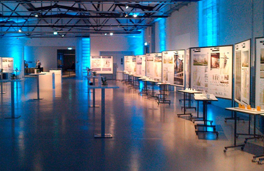 Ausstellungshalle eines Architekturwettbewerbs: weiße Pinnwände sind mit Postern bestückt, davor stehen Architekturmodelle auf Modelltischen.