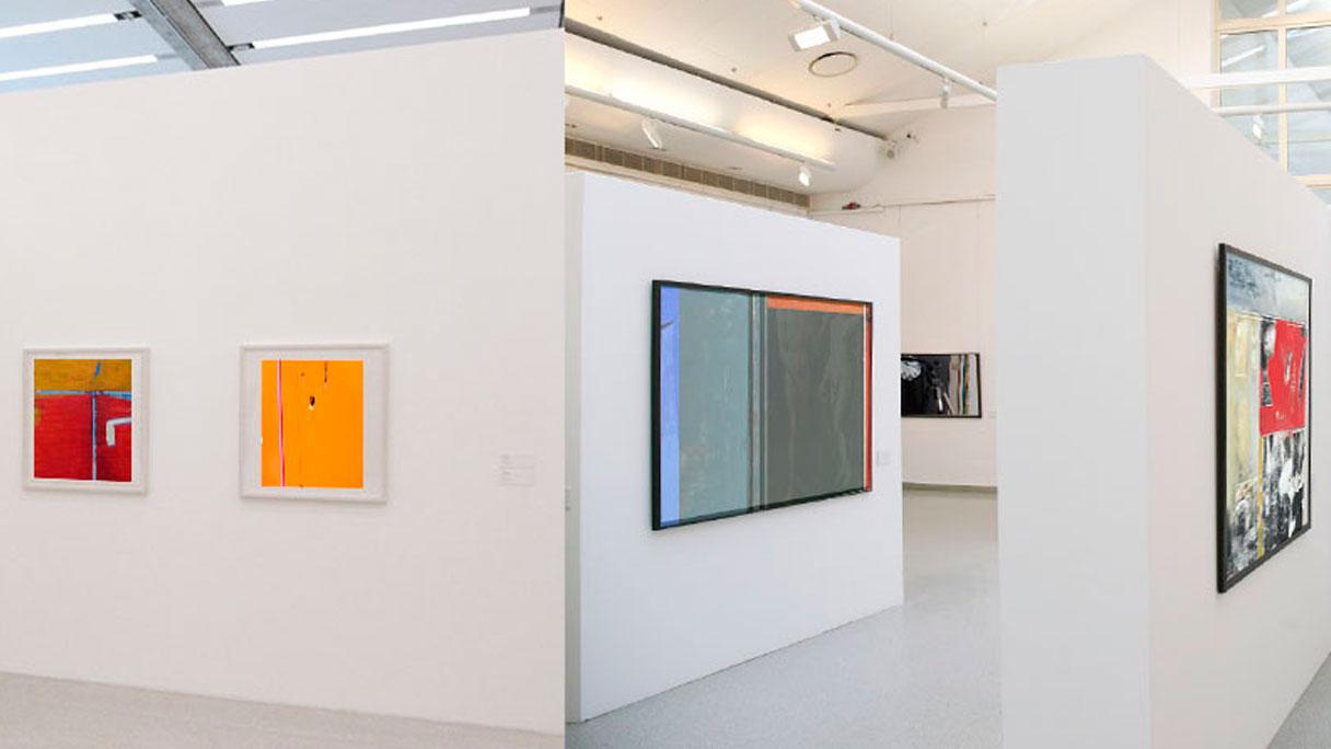 Ausstellungsbau: Ein Ausstellungsraum mit weißen Wänden, an denen Bilder in verschiedenen Größen gehängt sind.