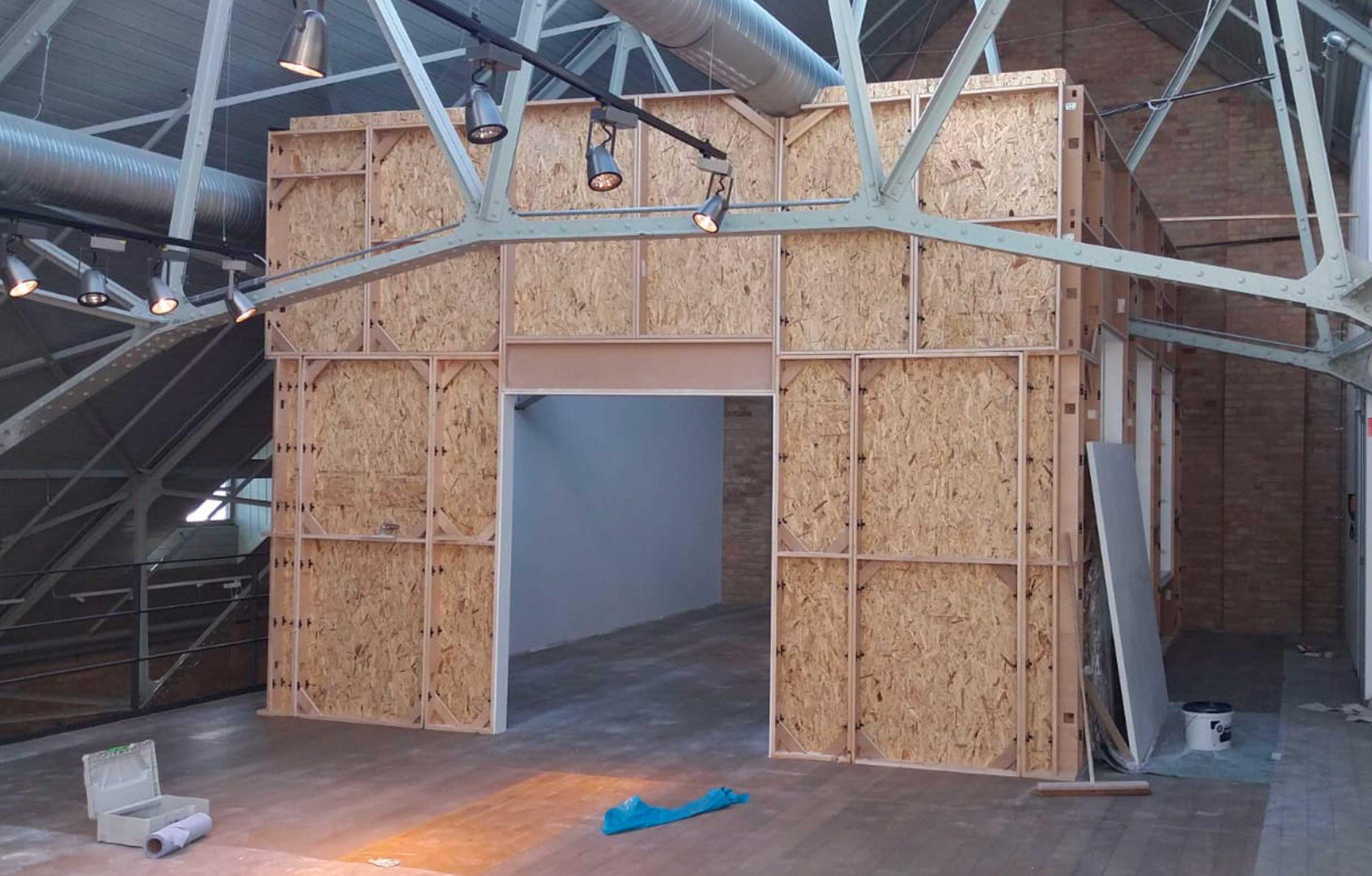 In einem Filmstudio wird ein Raum in eine Halle gebaut.