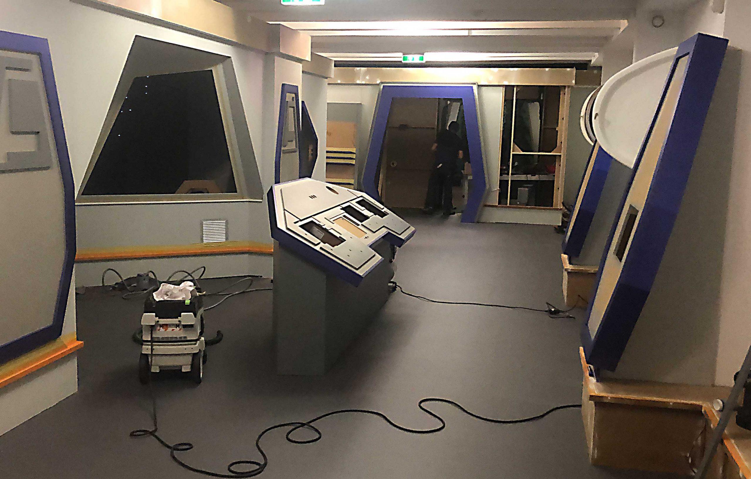 Der Aufbau der Sandmann-Ausstellung. Ein Raum mit rautenförmigen Fenstern, einem Bedienpult und anderen individuell gefertigten Ausstellungselementen.