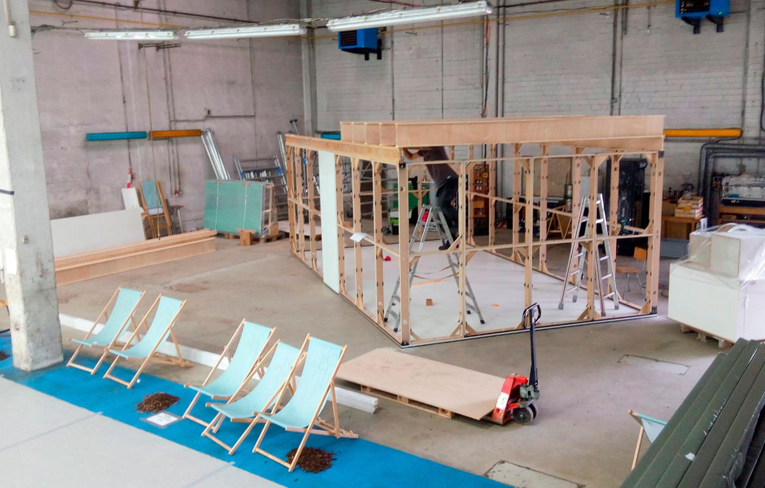 Messebau für Nike Location. Ein Raum im Raum wird gebaut, davor stehen Liegestühle.