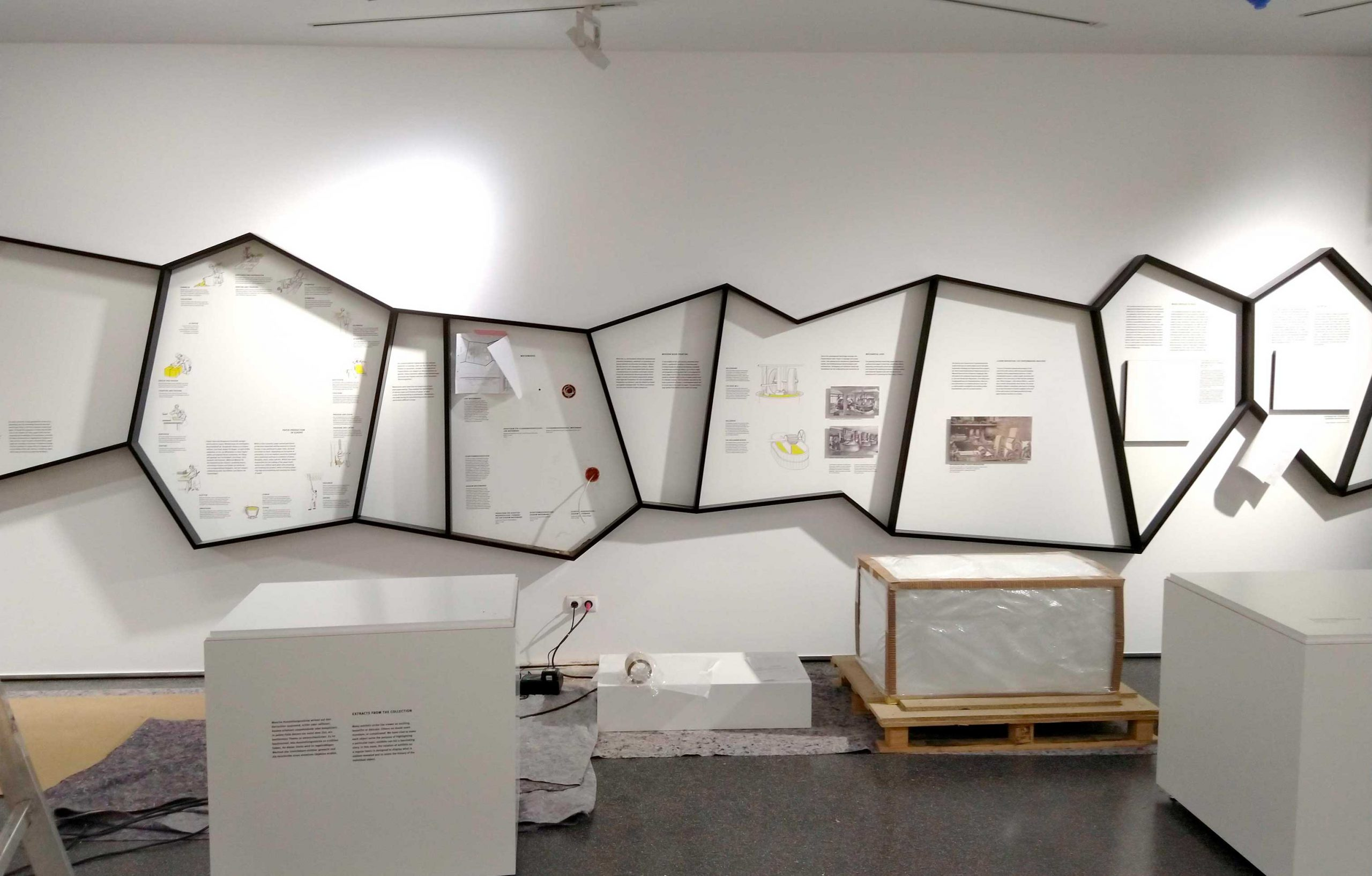 Im Papiermuseum Düren sind organisch geformte Ausstellungselemente an die Wand montiert.