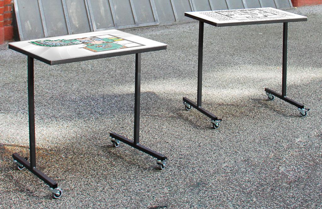 Zwei Architekturmodelltische auf Rollen in einer Ausstellungssituation. Darauf sind Grafiken zu sehen.