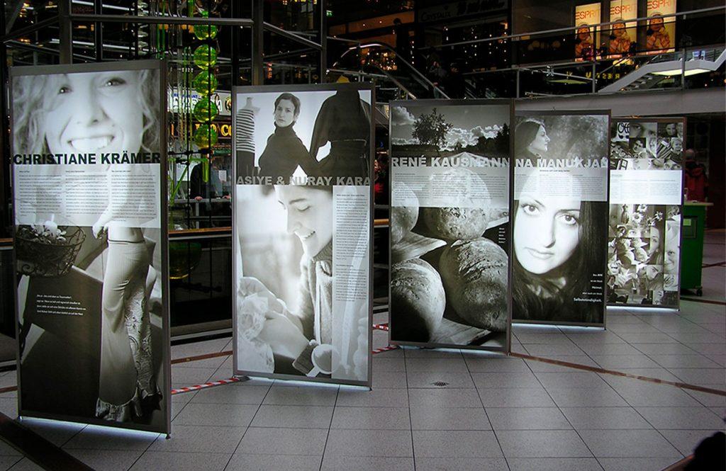 Octanorm Leuchttafeln sind mit schwarz-weiß Fotografien gestaltet und werden in einer Ausstellung genutzt.