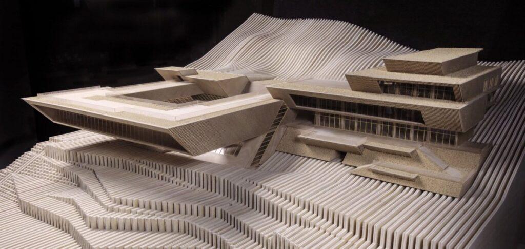 Ein Architekturmodell. Ein Haus ist spektakulär überhängend an einen Hang gebaut.