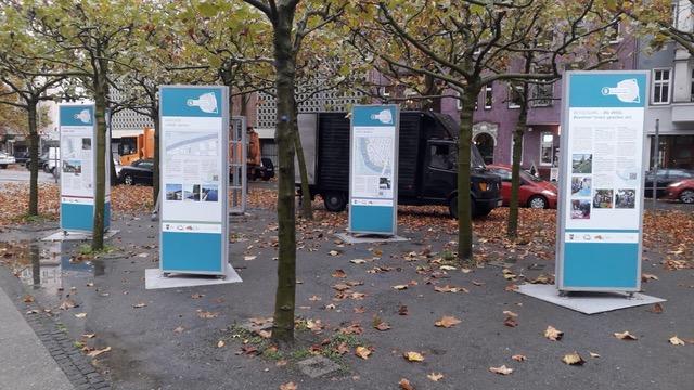 Outdoorstelen sind im Stadtraum zwischen Bäumen aufgebaut. Sie sind türkis gefärbt und mit Informationsgrafiken und Text bestückt.