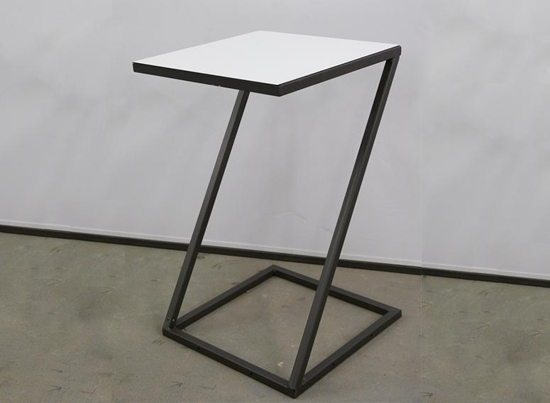 Der Modelltisch Z hat die Form des Buchstabens. Obenauf liegt eine weiße Tischplatte.